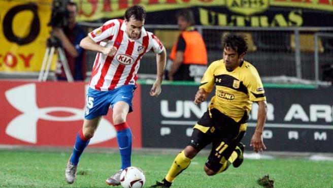 El uruguayo Diego Godín (i) del Atlético de Madrid lucha por el balón con Carlos Ruiz (d) del Aris de Salónica.