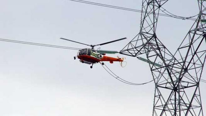 Un helicóptero revisando una línea eléctrica.