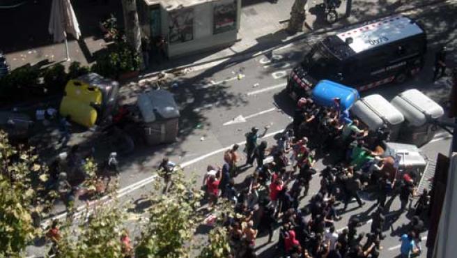 Un grupo de manifestantes crea una barricada con contenedores.