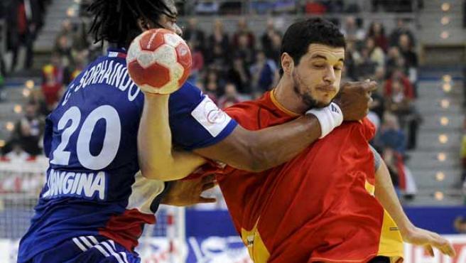El pivote francés Cedric Sorhaindo trata de detener el pase del lateral izquierdo español Alberto Entrerríos.