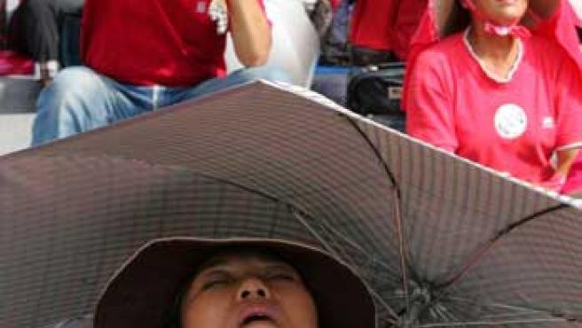 Una mujer duerme bajo un paraguas.