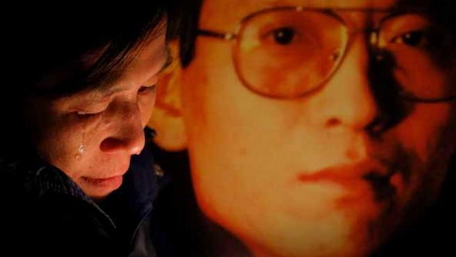 Fotografía de archivo de una activista llorando junto a una foto del disidente Liu Xiaobo
