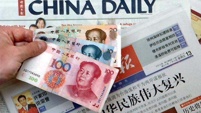 Billetes de yuanes sobre algunos periódicos chinos en Pekín.