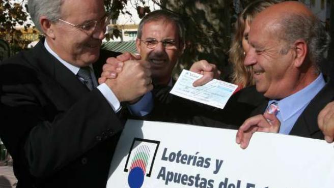 El director comercial de Loterías y Apuestas del Estado (izqda), entrega el cheque de 24,9 millones de euros a un acertante que ha conseguido el mayor premio de la historia de la Primitiva.