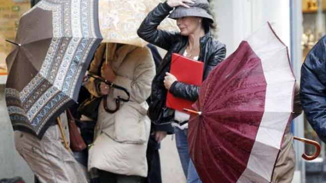 Varios transeúntes intentan controlar su paraguas en una céntrica calle de Santander debido al fuerte temporal de viento.