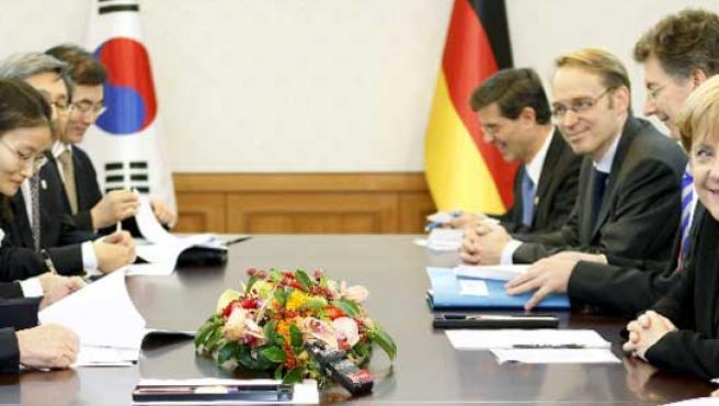 Angela Merkel (dcha), conversa con el primer ministro surcoreano, Kim Hwang-sik (izq), durante un encuentro bilateral celebrado en el ámbito de la cumbre del G20 en Seúl.