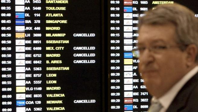 Un hombre pasa por delante de un panel de vuelos del aeropuerto de El Prat de Barcelona.