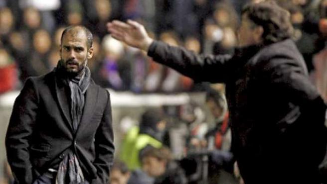 El entrenador del F.C Barcelona, Pep Guardiola (i), observa las indicaciones del técnico de Osasuna, Camacho.