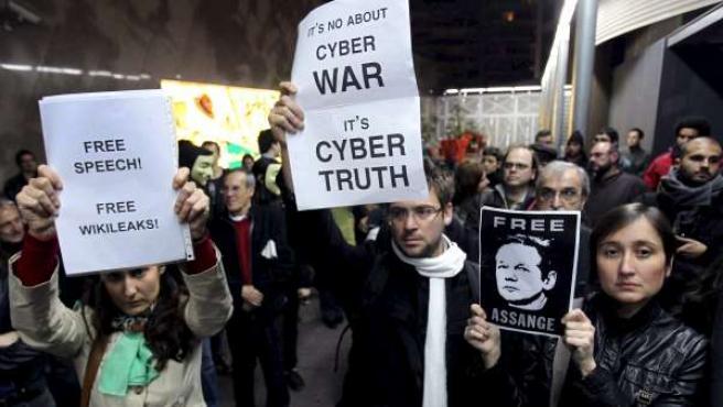 Varios manifestantes muestran carteles durante la concentración, convocada este sábado por la plataforma Free Wikileaks, ante el consulado del Reino Unido en Barcelona.
