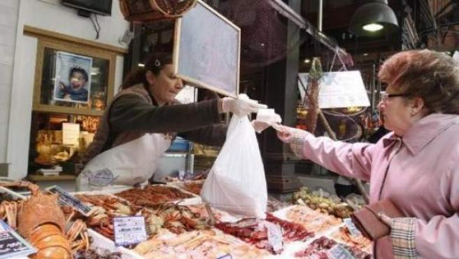 Una mujer hace la compra en una pescadería.