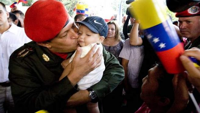 Hugo Chávez besa a un bebé durante una visita a una zona afectada por las lluvias.