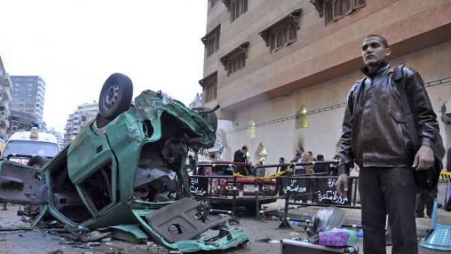 Un policía egipcio espera junto a los restos del vehículo en el que viajaría el supuesto terrorista suicida frente a la iglesia cristiana de Al Qidiseen (Los Santos) de la ciudad de Alejandría (Egipto).