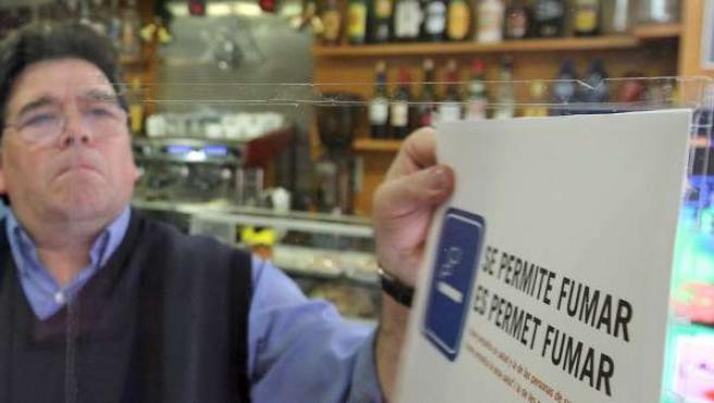 El encargado de un pequeño bar en Valencia retira el cartel de 'permitido fumar' un día antes de la entrada en vigor de la nueva Ley del Tabaco.