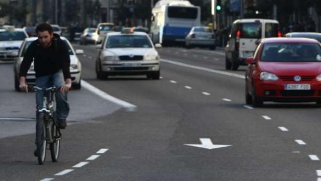 Un ciclista circula por un lateral de la Gran Vía en medio del tráfico.