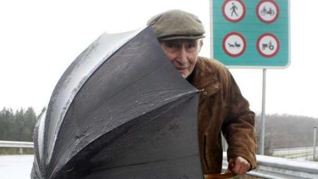Un hombre se protege de la lluvia.
