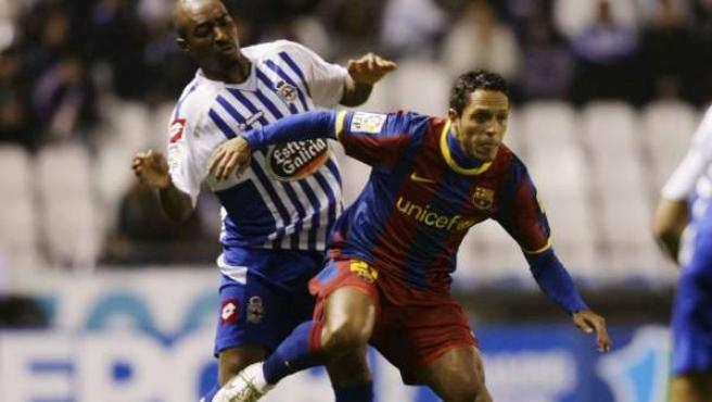 Adriano Correia, lateral del Barcelona, pelea por un balón con Yves Desmarets, centrocampista del Deportivo.