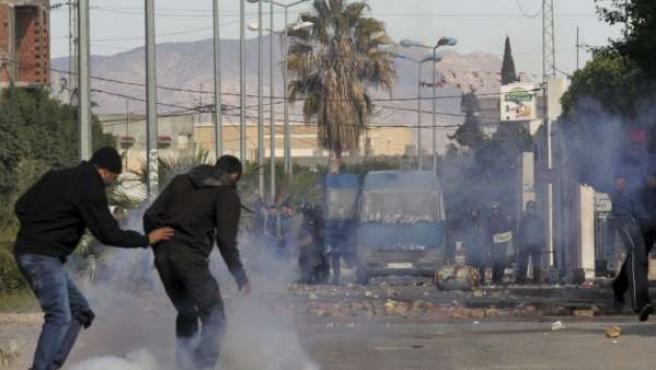 Un grupo de jóvenes intenta esquivar las bombas de gases lacrimógenos durante los enfrentamientos del lunes.
