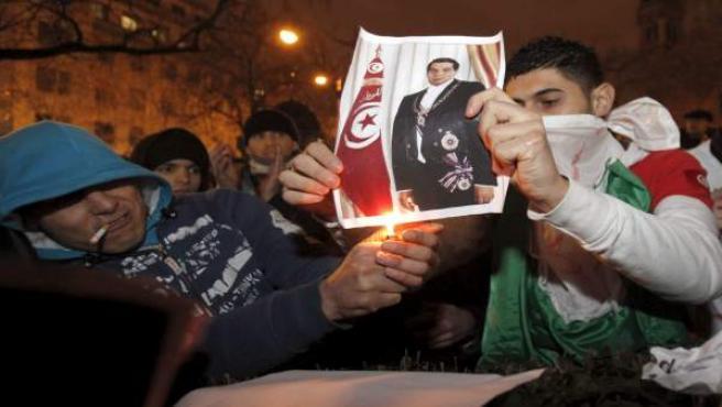 Unos jóvenes queman el retrato del presidente Ben Alí en una protesta.