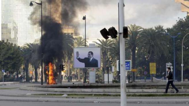 El humo de un incendio causado por unos manifestantes se ve detrás de un cartel del presidente tunecino, Zine el Abidine Ben Alí