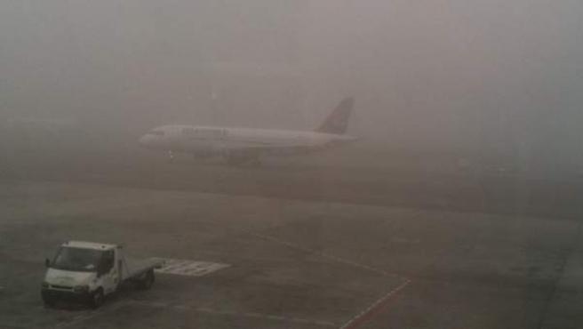 Un avión, estacionado en un aeropuerto en un día de intensa niebla.