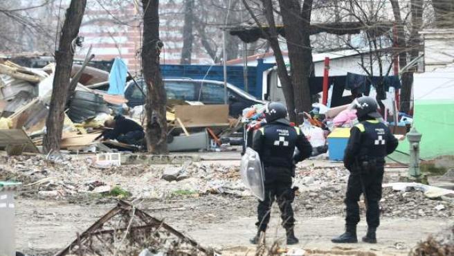 Dos agentes de Policía vigilan el derribo de varias viviendas en el poblado de Puerta del Hierro.