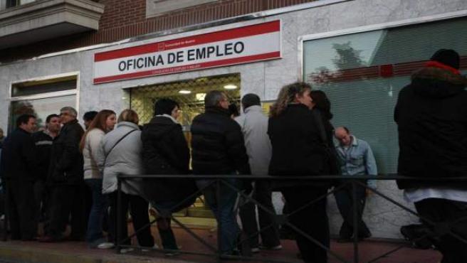 Varios parados hacen cola ante una oficina de empleo.