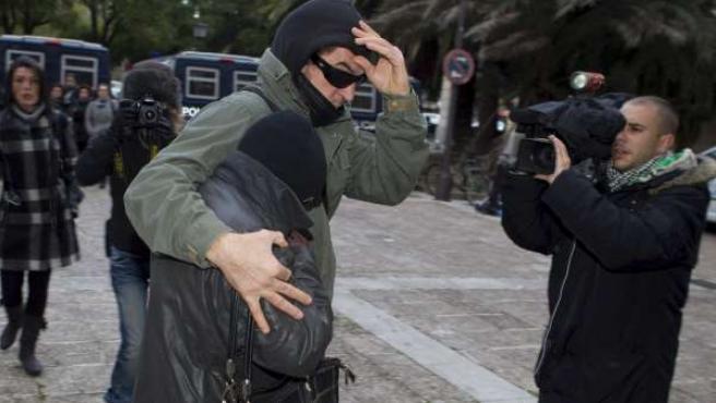 La madre de Javier G.M., apodado 'El Cuco' (con la cara tapada y agazapada entre el brazo de un acompañante), llega al edificio de la Audiencia de Sevilla.