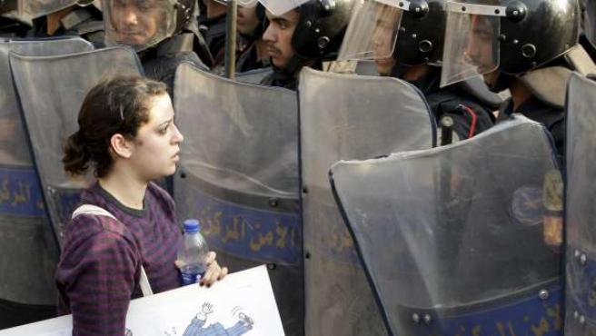 Una joven habla con un policía antidisturbios durante una concentración en El Cairo.