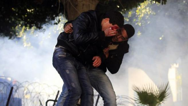 Un manifestante protege a un herido durante los enfrentamientos contra la Policía en Túnez. Las protestas se siguen produciendo en el país mientras la Justicia tunecina ha dictado una orden de detención internacional contra el expresidente Ben Alí y su esposa.