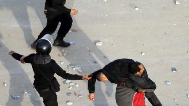 Unos policías cargan con un compañero herido durante las protestas en Egipto.