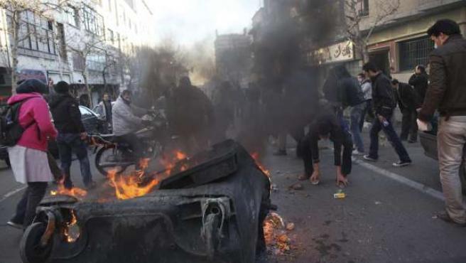 Los manifestantes queman contenedores en las calles de Teherán durante unas protestas.