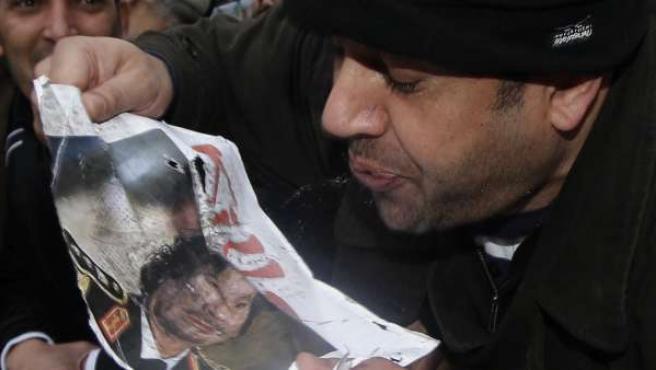 Un manifestante anti Gadafi escupe sobre una imagen del presidente libio durante las protestas en Londres ante la embajada de Libia.