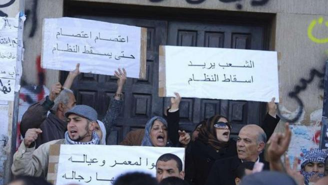 """Un grupo de manifestantes en Bengasi sostienen pancartas en las que se lee """"Queremos que caiga el régimen""""."""