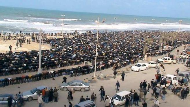 Centenares de libios contrarios a Gadafi rezan en una playa de Bengasi.
