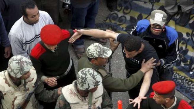 Soldados egipcios intentan frenar a los centenares de egipcios que insisten en no abandonar la plaza Tahrir.
