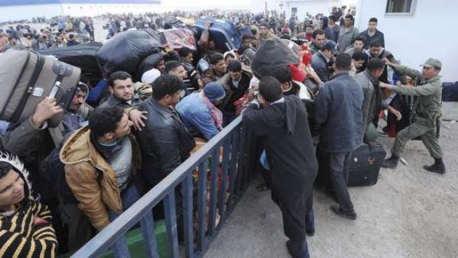 Una multitud se agolpa junto a una valla en la localidad libia de Tas Jedir, fronteriza con Túnez, donde miles de ciudadanos libios, egipcios, tunecinos e indios intentan entrar en Túnez para escapar de las fuerzas de seguridad libias.