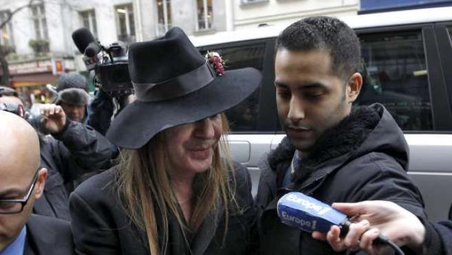 La prensa rodea a John Galliano en la puerta de la comisaría.