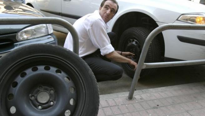 Un hombre cambia una rueda de su coche en Córdoba, en una imagen de archivo de 2006.