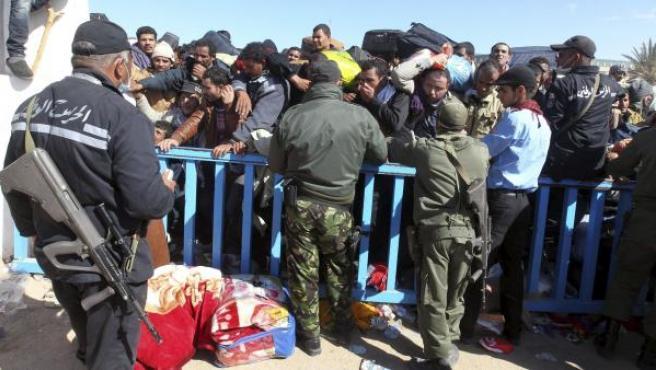Policías y militares tratan de controlar el flujo de refugiados egipcios que abandonan Libia en el paso fronterizo de Ras el Jebir, Túnez.