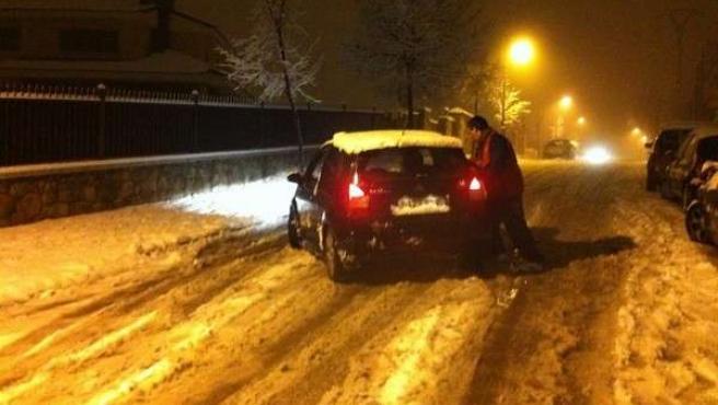 Un hombre empuja su coche, atrapado por la intensa nevada caída entre Las Rozas y Guadarrama.