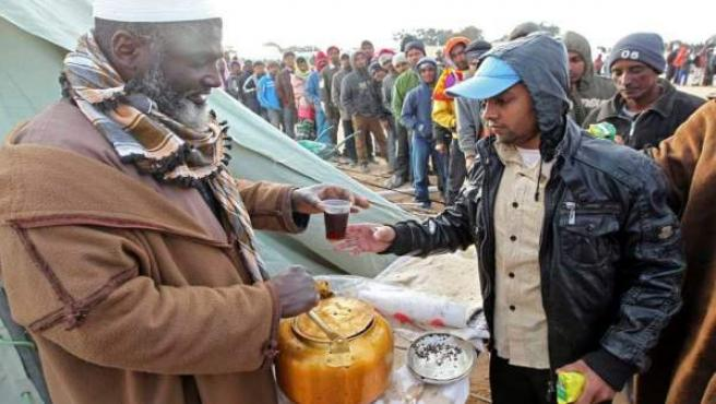 Trabajadores bangladesíes que abandonaron Libia por la frontera de Túnez, reciben alimentos en el campo de refugiados de Chucha, junto a la frontera de Ras el Jedir (Túnez).