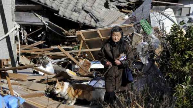 Una mujer pasea con su perro entre los escombros de varias casas destruidas por el maremoto que arrasó la localidad de Iwaki, en la prefectura de Fukushima (Japón).