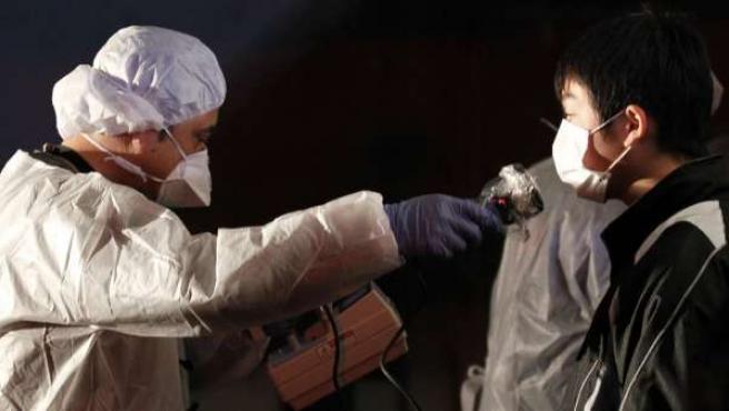 Un miembro del equipo de protección explora a un hombre en busca de signos de la radiación.