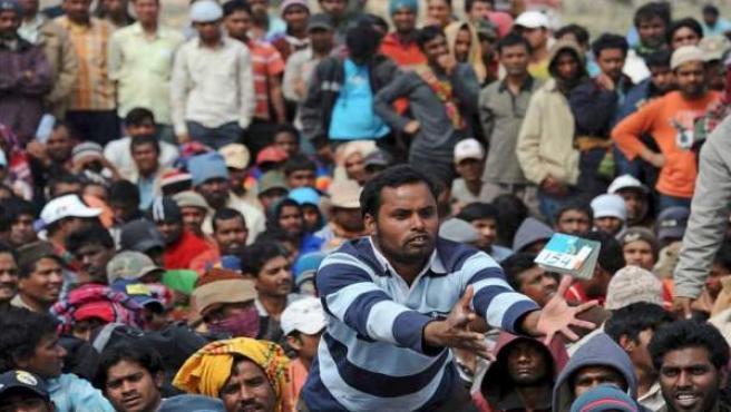 Un trabajador bengalí que huyó de Libia recoge su pasaporte en el campamento de refugiados levantado por ACNUR cerca de Ras el Jedir, Túnez.