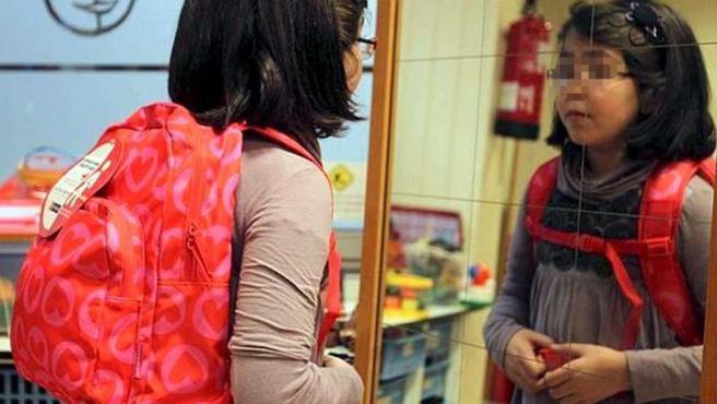 Una niña con su mochila a cuestas se mira en el espejo.