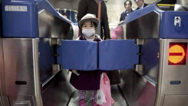 Una niña espera tras un torno cerrado antes de coger un Shinkansen, el tren bala japonés, para abandonar Tokio.