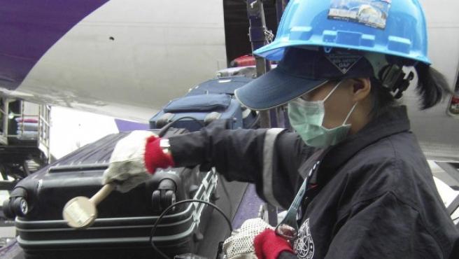 Un agente tailandés mide los niveles de radiación en equipaje procedente de Japón en el aeropuerto de Bangkok.