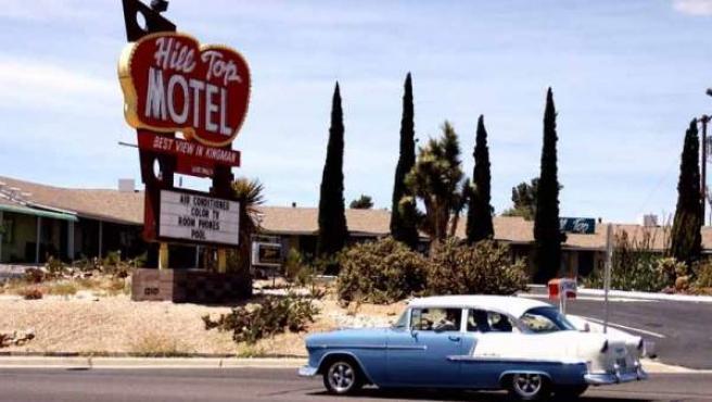 Un automóvil clásico pasando junto a un Motel.
