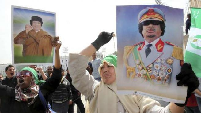 Simpatizantes del líder libio Muamar al Gadafi sostienen carteles con su fotografía durante una nueva concentración en su apoyo celebrada en Trípoli (Libia).