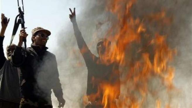 Combatientes insurrectos gritan junto a un fuego en la carretera libia de Bengasi a Ajdabiya.